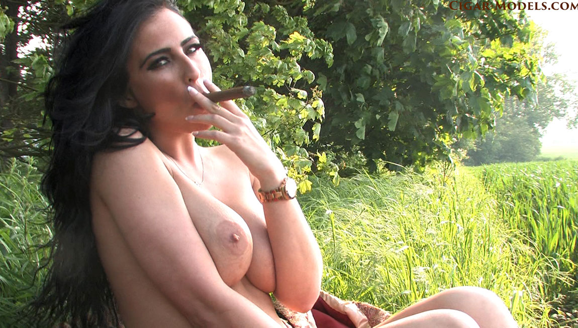 Sophie L smoking a cigar topless